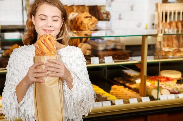 Desejando a primeira mordida. retrato de meio corpo de uma mulher muito alegre cheirando a pão fresco e sorrindo alegremente