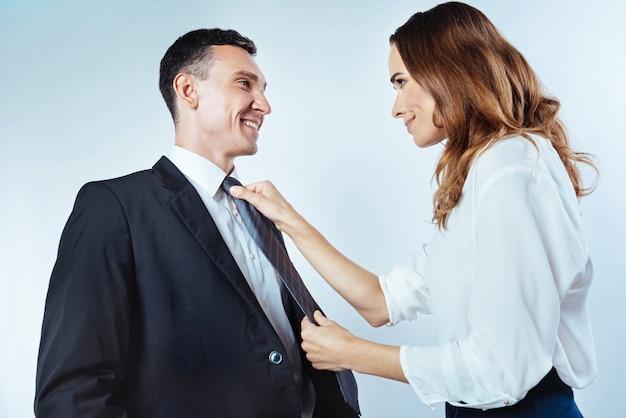 Desejo a você boa sorte hoje. vista lateral em um casal de negócios de sucesso, olhando um para o outro enquanto atenta jovem ajustando uma gravata do marido.