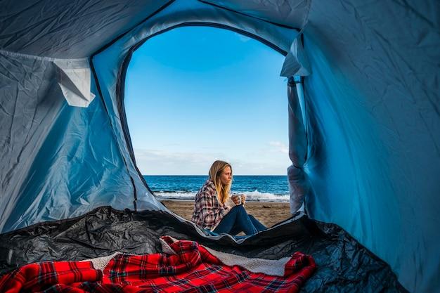 Desejo de viajar e estilo de vida alternativo de férias para uma linda garota loira sentada do lado de fora de uma barraca acampada na areia da praia em frente às ondas do oceano
