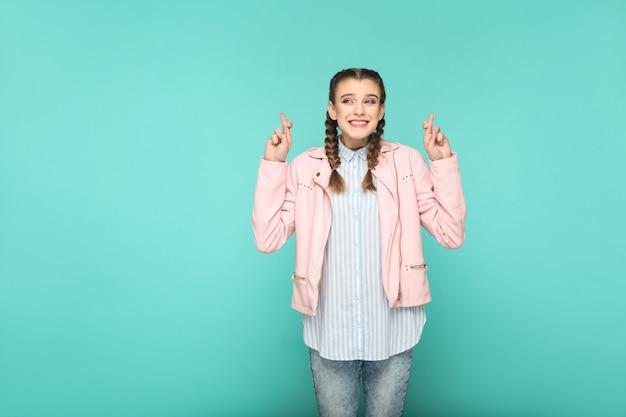 Desejo esperançoso retrato de linda linda garota em pé com maquiagem e penteado pigtail marrom na jaqueta rosa camisa azul claro listrada. indoor, studio shot isolado em fundo azul ou verde.