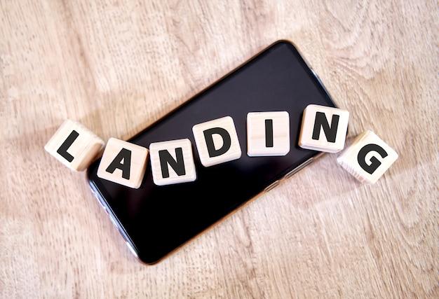 Desembarque de texto em cubos de madeira em um smartphone preto. cubos colocaram em um smartphone preto na mesa de madeira.
