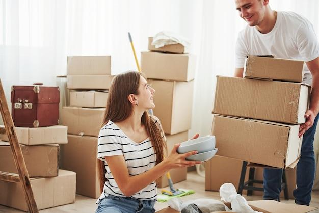 Desempacotando caixas. casal jovem alegre em seu novo apartamento. concepção de movimento.