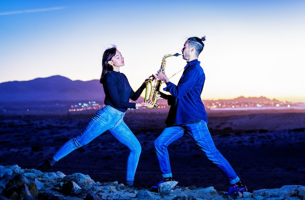 Desempenho de casal axofonista e dançarino contra a hora azul e as mãos da lua