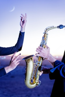 Desempenho de saxofonista e mãos femininas contra a exibição das horas azuis e dos ponteiros da lua