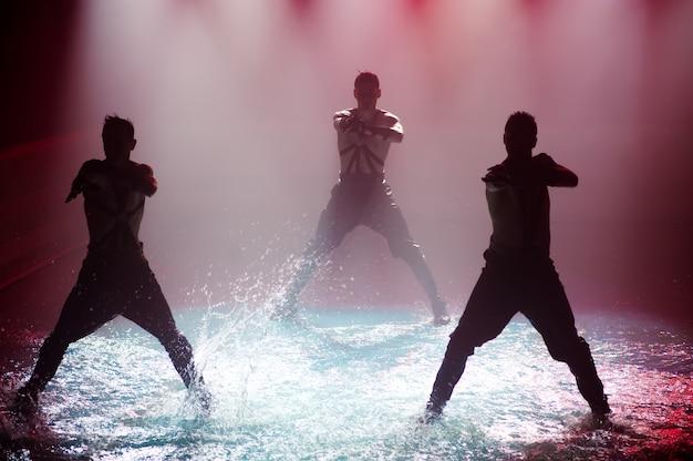 Desempenho na água de um grupo de dança contra a luz do clube.