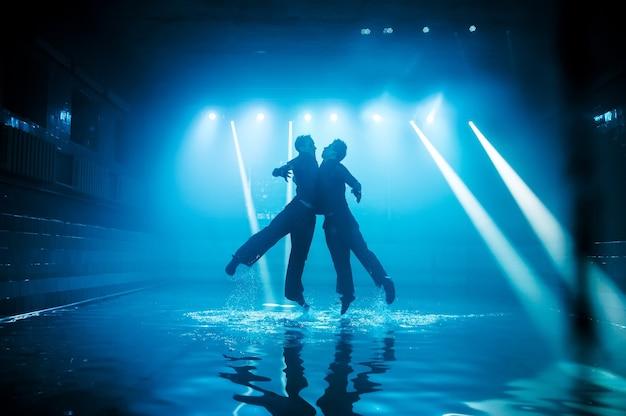 Desempenho na água de um grupo de dança no contexto da luz do clube.