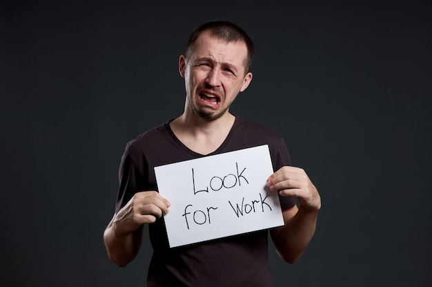 Desemprego e crise. homem mantém um sinal com as palavras à procura de trabalho