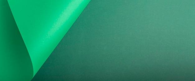 Desenha o plano de fundo curvo de papelão verde. vista superior, configuração plana. bandeira.