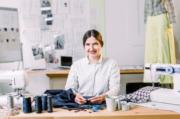 Desenhador de moda fêmea de sorriso que senta-se na mesa de escritório. costureira, alfaiate, obras e costureira conceito - retrato do designer de moda sorridente usando a máquina de costura