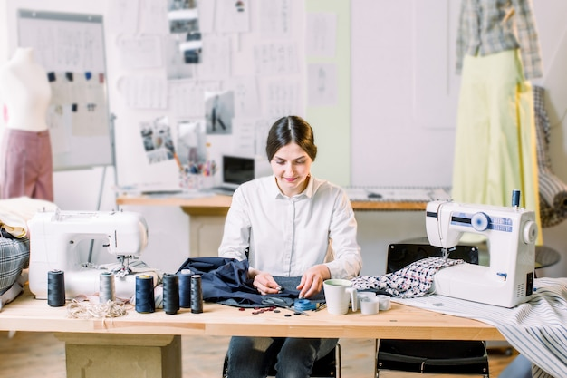 Desenhador de moda fêmea de sorriso que senta-se na mesa de escritório. jovem mulher que costura com a máquina de costura no estúdio ao sentar-se em seu local de trabalho.