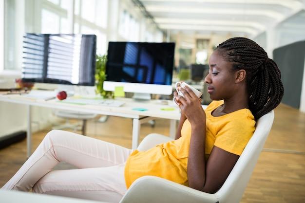 Desenhador gráfico fêmea que come o café