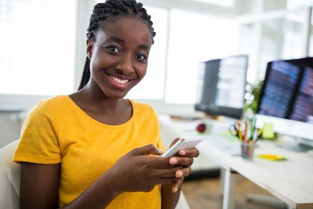 Desenhador gráfico fêmea que usa o telefone móvel