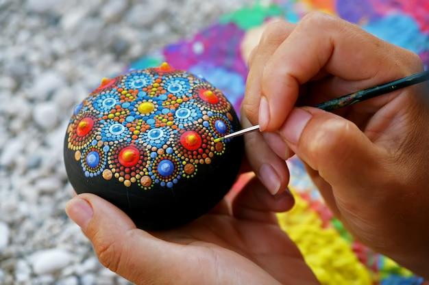 Desenhando com um pincel uma mandala em uma pedra