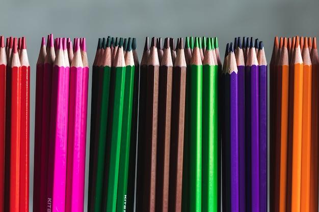 Desenhando lápis de madeira coloridos em um arco-íris linha em cinza
