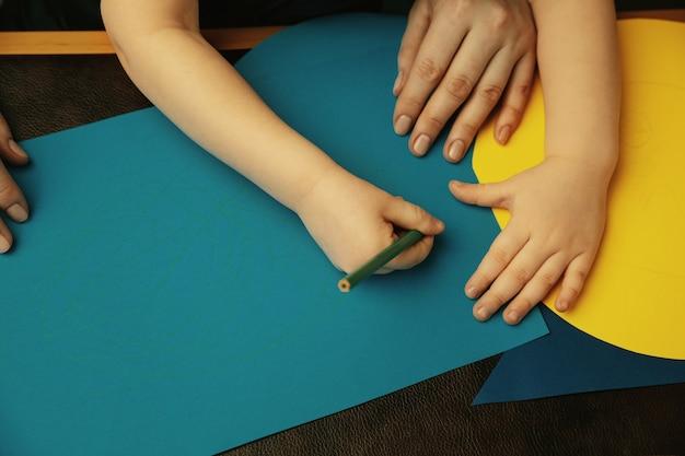Desenho com pensils coloridos. close-up tiro das mãos femininas e infantis fazendo coisas diferentes juntos. família, casa, educação, infância, conceito de caridade. mãe e filho ou filha, riqueza.