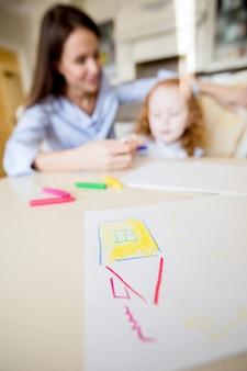 Desenho criançola da casa na tabela e na família