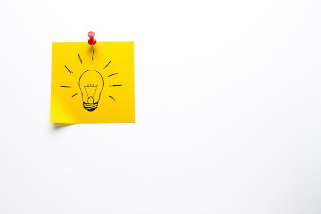 Desenho criativo de uma lâmpada em uma etiqueta amarela. o conceito de novas idéias, inovações, soluções para problemas.