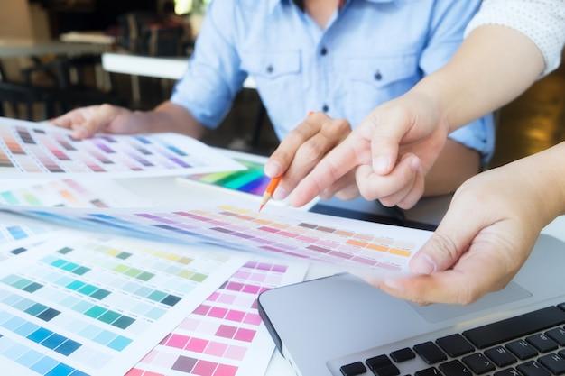 Desenho de artista no tablet gráfico com amostras de cores no escritório.