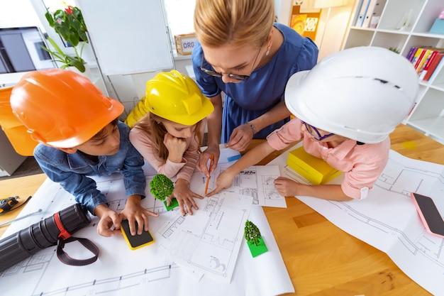 Desenho de esboços. dois meninos e uma menina usando capacetes brilhantes fazendo esboços com o professor