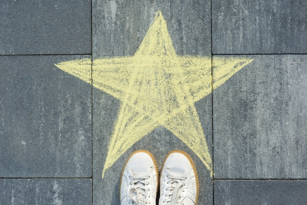 Desenho de giz de cera na estrela e nos pés do asfalto.
