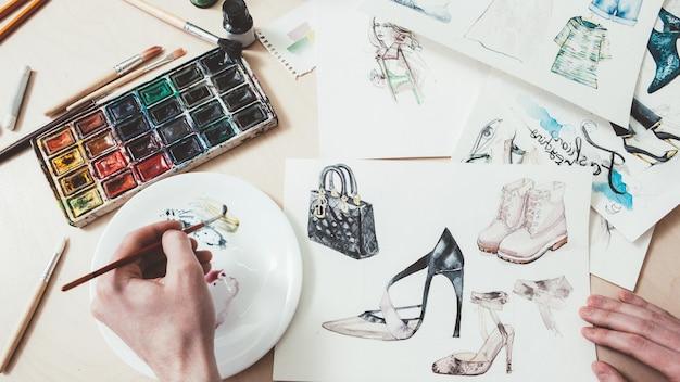 Desenho de moda. design de roupas femininas. artista masculino pintando com aquarelas.