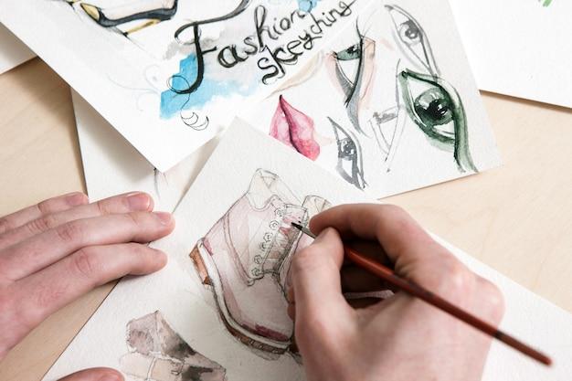 Desenho de moda em processo de design. homem ou mulher irreconhecível desenha um modelo de calçado na mesa