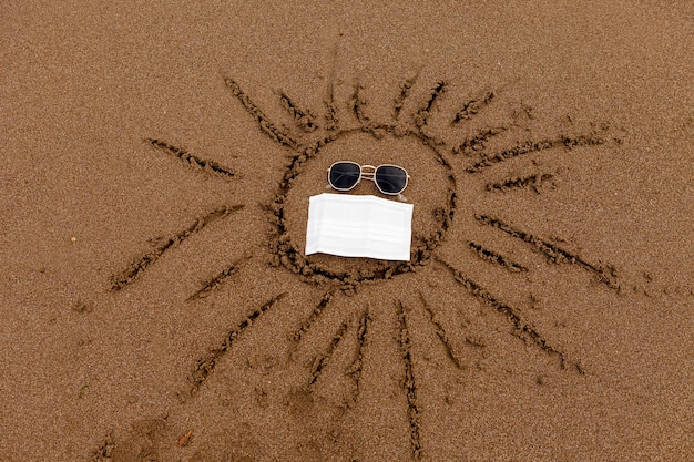 Desenho de óculos de sol e máscara médica na areia da praia de descanso no mar e na costa durante o ...