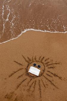 Desenho de óculos de sol e uma máscara médica na areia da praia. descanse no mar e na costa durante a pandemia.