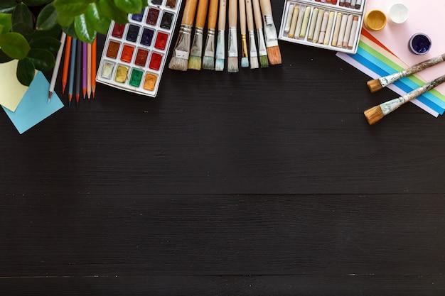 Desenho de pintura de arte criativa fornece ferramentas definidas na vista superior de mesa de madeira