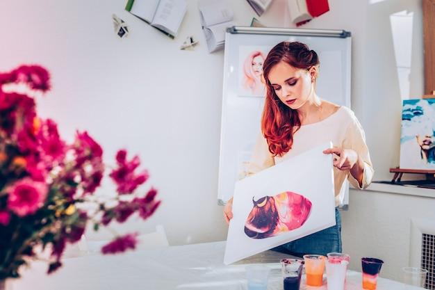 Desenho de tintas. uma promissora artista ruiva e cacheada desenhando tintas na pintura de mármore
