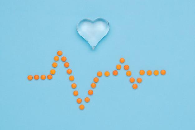 Desenho de um cardiograma feito de pílulas laranja e um coração de vidro em uma superfície azul