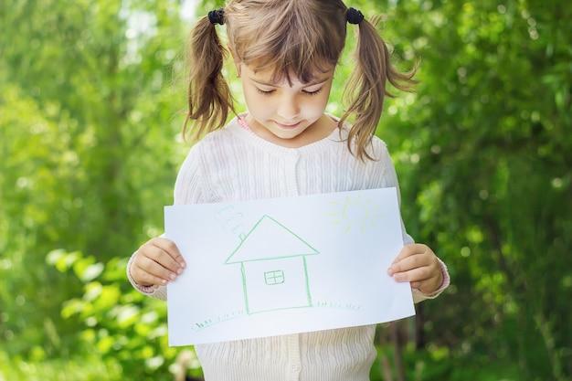Desenho de uma casa verde nas mãos de uma criança.