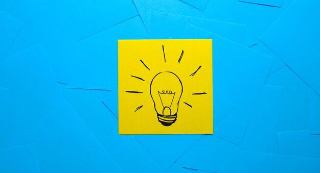Desenho de uma lâmpada em um adesivo amarelo