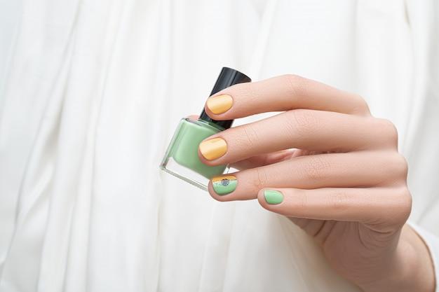 Desenho de unha verde e amarelo. mão feminina com arte de unha verde segurando esmalte verde.