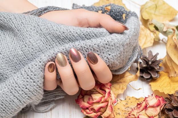 Desenho de unhas de ouro autunm. mãos de mulher seguram um xale de lã cinza.