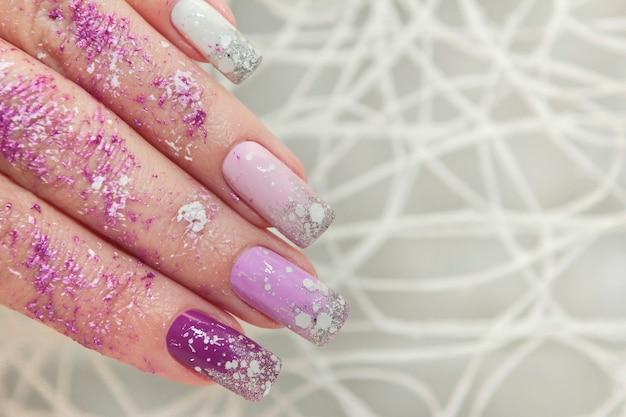Desenho de unhas roxo multicolorido com glitter
