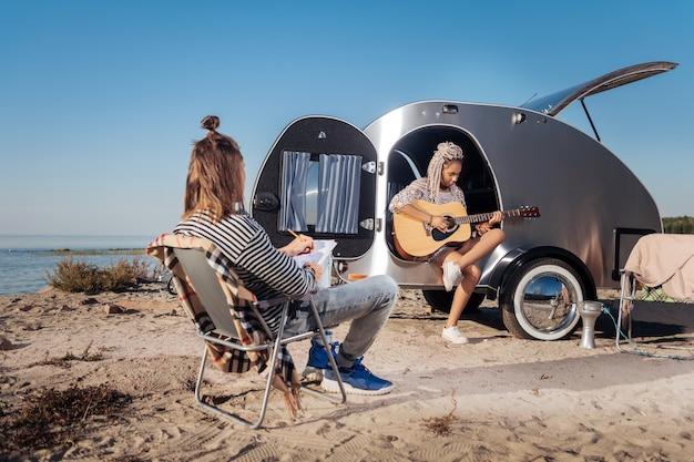 Desenho e música. homem de cabelos loiros se sentindo inspirado desenhando a natureza enquanto sua namorada tocando violão