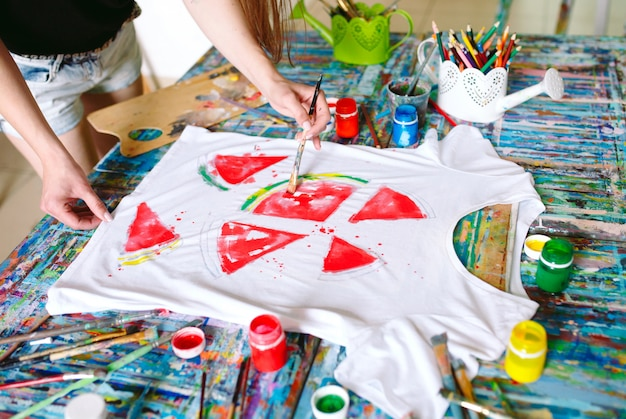 Desenho em roupas. garota desenha em uma camiseta branca.