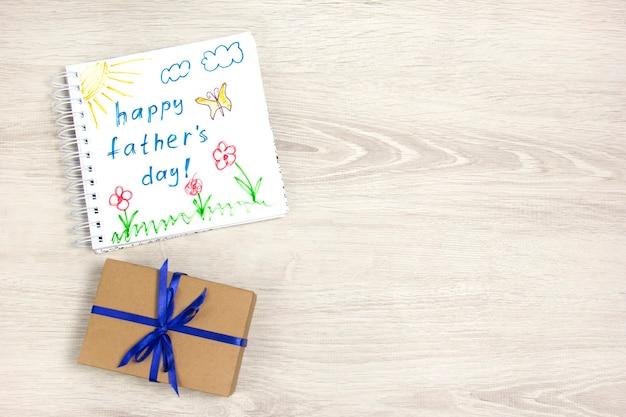 Desenho infantil do feliz dia dos pais usando um lápis uma caixa de presente com uma fita azul
