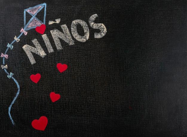 Desenho na lixa. niños (espanhol) escrito no quadro-negro e corações. espaço de cópia de plano de fundo