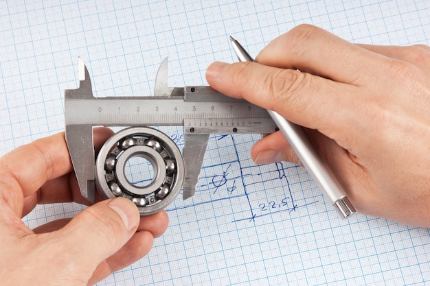 Desenho técnico e pinças com rolamento na mão em papel milimetrado