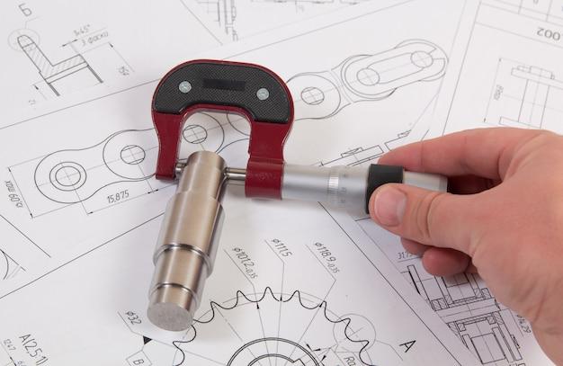 Desenho técnico, micrômetro e corrente de roletes. engenharia, tecnologia e trabalho em metal. medição de micrômetro de detalhes da cadeia industrial.