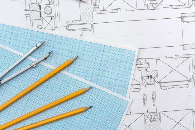 Desenho técnico, papel milimetrado e ferramentas. equipe de escritório de engenheiro trabalhando com plantas.