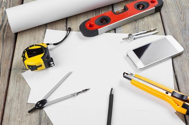 Desenhos arquitetônicos. instrumentos na mesa de trabalho. folha de papel em branco