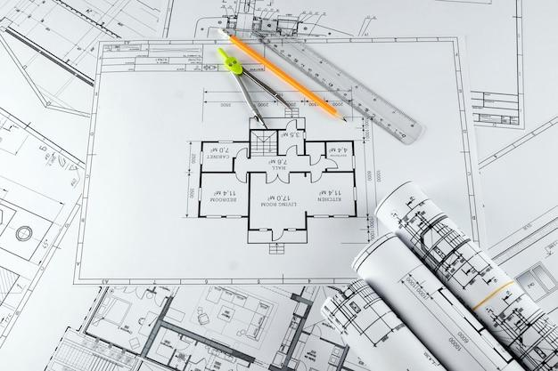 Desenhos de construção arquitetônica torcidos em um rolo, projetos de construção em papel.