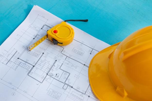Desenhos de construção, capacetes de segurança e fita métrica na superfície de madeira azul