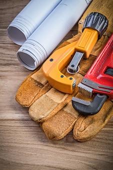 Desenhos de construção, luvas de segurança, chave de macaco, cortador de tubos no conceito de encanamento de tábuas de madeira