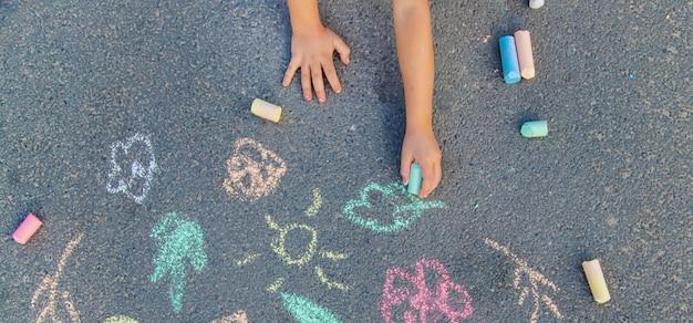 Desenhos de crianças no asfalto com giz
