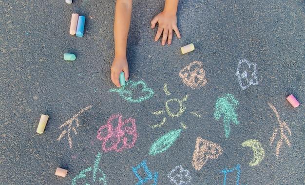 Desenhos de crianças no asfalto com giz.