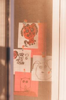 Desenhos de crianças por trás da janela